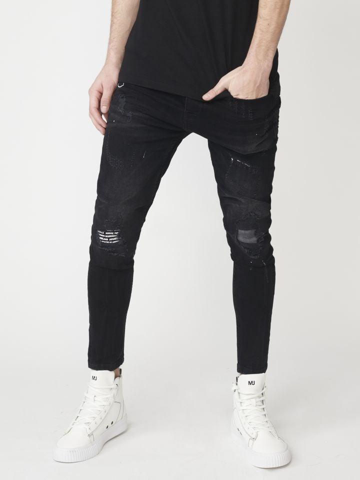 מכנסי ג`ינס בעיטור קרעים אטומים ורוכנסי קרסול .
